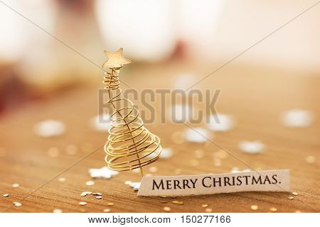 Merry Christmas background with christmas tree made from gold or brass wires and star glitter. Focus on