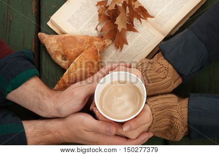 Hands of young lovers holding a hot cup of coffee on autumn background. Old book autumn leaves on wooden background. Concept cozy coffee cup. Top view