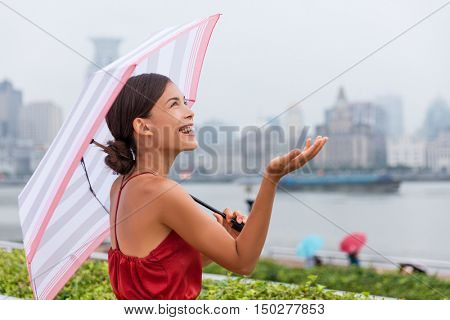 Rain, weather concept - happy Asian tourist woman under umbrella holding hand up checking the amount of raindrops during city walk on Shanghai waterfront harbour. Young chinese businesswoman.