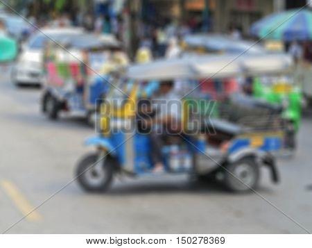 Blurred background : Blue Tuk Tuk in street road Bangkok , Thailand blur background