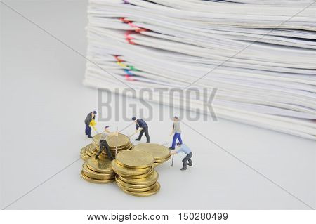 Miniature People With Gold Coins And Pile Overload Document