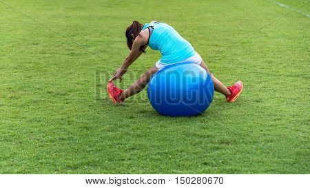Young woman doing sit ups in a park on an exercise ballsoft focus