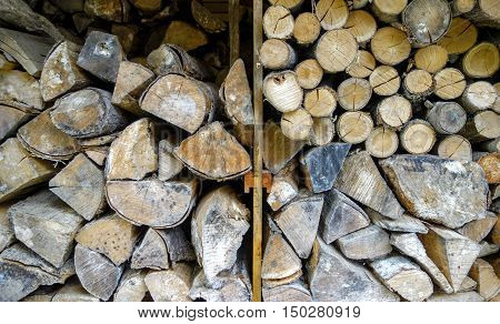 Wall of diverse rugged firewood logs stacked in a rural Maine wood shed.