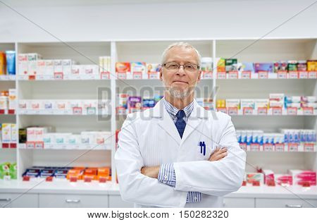medicine, pharmacy, people, health care and pharmacology concept - smiling senior male pharmacist in white coat at drugstore