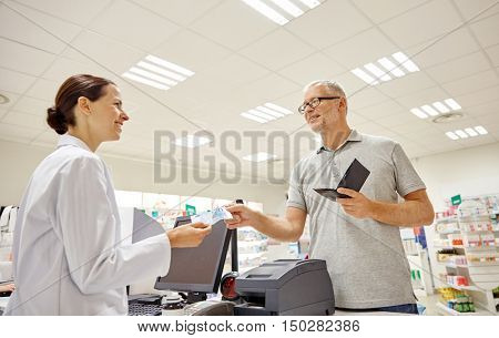 medicine, pharmaceutics, health care and people concept - smiling senior man with wallet giving money to pharmacist at drugstore cash register