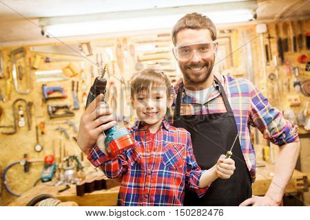 family, carpentry, woodwork and people concept - happy father and little son with drill and screwdriver working at workshop