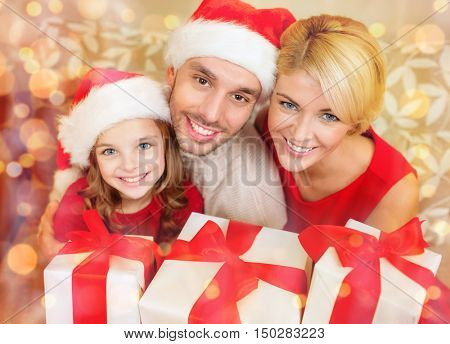 family, christmas, x-mas, happiness and people concept - smiling family in santa helper hats with many gift boxes
