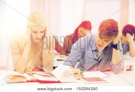 education, technology and internet concept - tired students with tablet pc, books and notebooks preparing for exam