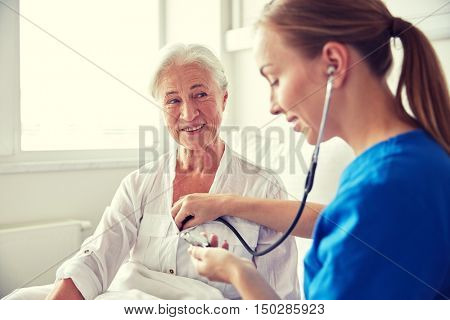 medicine, age, support, health care and people concept - doctor or nurse with stethoscope visiting senior woman and checking her heartbeat at hospital ward