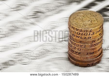 Sterling pound depreciation devaluation reduction value concept closeup macro view at UK currency stack of one pound coins