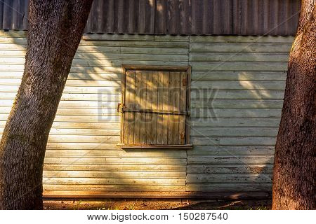 A closed window on an old storage wall. The autumn sun cast strong shadows on the wooden wall.