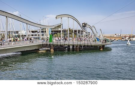 BARCELONA SPAIN - JULY 4 2016: Marina Port Vell and the Rambla del Mar in Barcelona. Ramblas del Mar are a wooden bridge built in 1994.