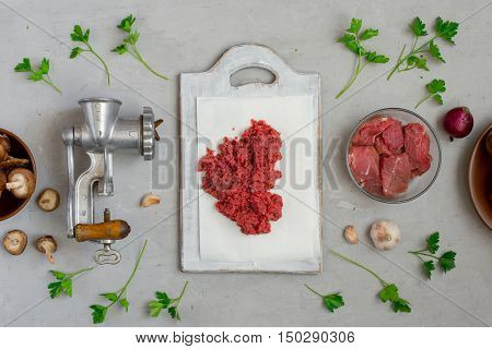 Raw ground beef on kitchen cutting board with the ingredients for the preparation of useful food top view