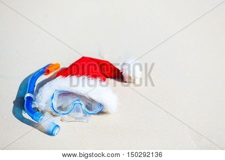 Snorkeling equipment mask and snorkel and red Santa hat on tropical white sand beach