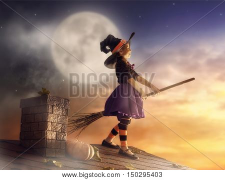 Happy Halloween! Cute little witch with a broomstick. Beautiful young child girl in witch costume on the roof.