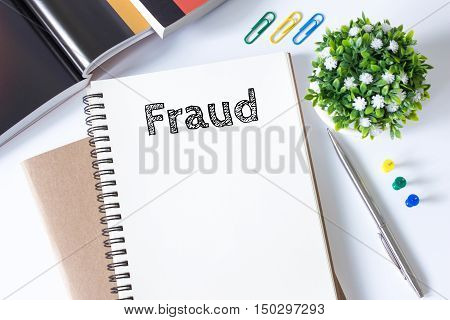 fraud word message on white paper book and copy space on white desk / business concept / top view
