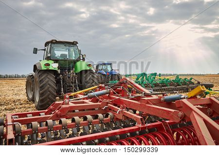 Two tractor with plow working in the field, a farmer riding a tractor, agricultural machinery in the work, tractor in the background cloudy sky