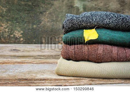 Pile of colorful warm clothes and yellow leaf on wooden background. Toned image.
