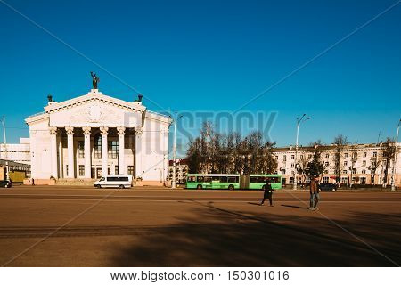 Gomel Belarus - March 27 2016: City transport and people walking on Lenin Square near Gomel Drama Theatre