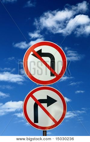 two opposite road signs against blue sky and clouds