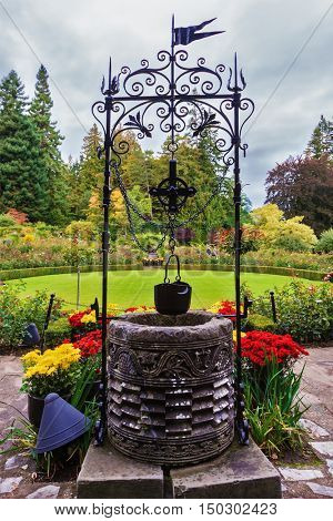 Scenic decorative park Butchart Gardens on Vancouver Island, Canada. Decorative well on the green lawn