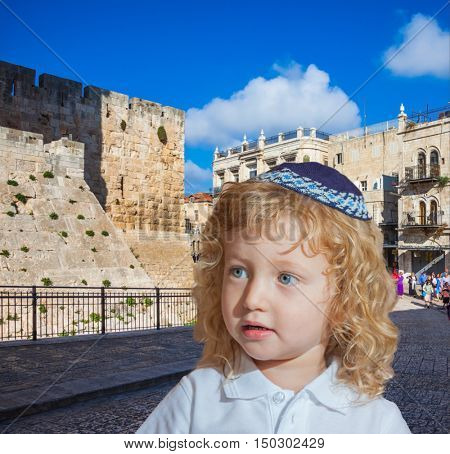 Adorable Jewish child in a blue yarmulke. Little boy with long blond curls and blue eyes. Jerusalem, the city of King David