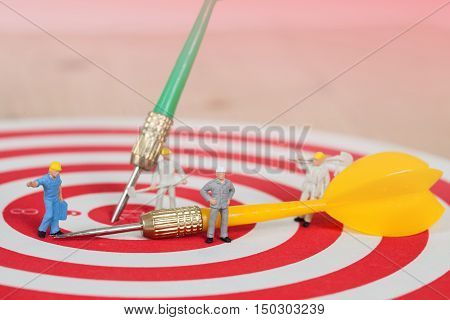 Miniature worker toy on red dart board with yellow dart arrow
