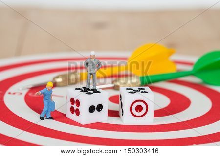 Miniature worker toy with dice on red dart board with yellow dart arrow