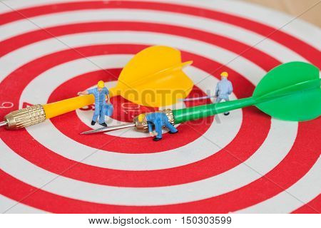 Miniature worker toy on red dart board with green dart arrow