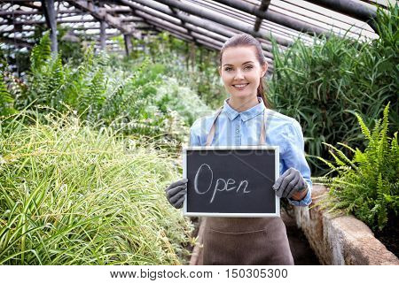 Pretty young gardener holding board with inscription OPEN