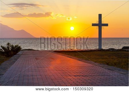 Silhouette of cross at sunrise or sunset with light rays and sea panorama, Athos, Greece