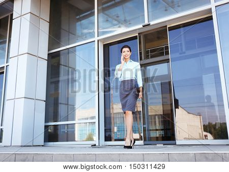 Beautiful businesswoman with cellphone and clipboard near office