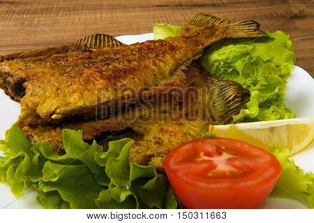 Fried Fish flounder on white plate with lettuce tomato and lemon on wooden background