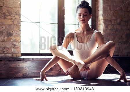 Concentrated and relaxed. Beautiful elegant young girl having her yoga classes and doing lotus posture while training in a gym.