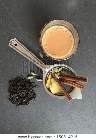 Flavorsome Indian spiced tea made with cardamom, cinammon and ginger. A glass full of 'Karak chai' placed with metal sieve and ingredients. View from above.