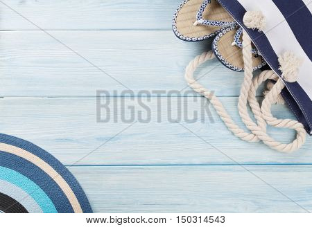 Beach accessories. Bag with flip-flops and sun hat on wooden background. Top view with copy space