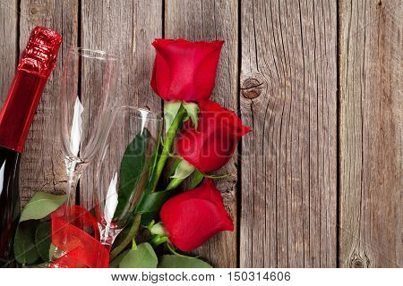 Valentines day roses bouquet and champagne on wooden table. Top view with copy space