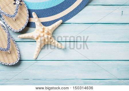 Beach accessories. Flip flops, hat and starfish on wooden background. Top view with copy space