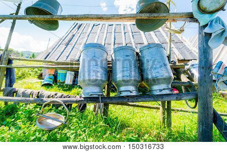 Old Milk Cans Made of Aluminum. Old milk cans made of metal to dry on a wooden stand - upside down - shallow depth of field
