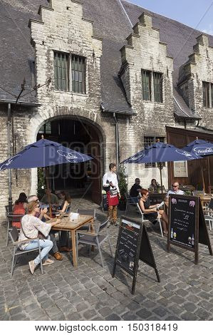 Ghent, Belgium, 27 august 2016: waiter waits on tourists at outdoor cafe in centre of the medieval town Ghent in Belgium