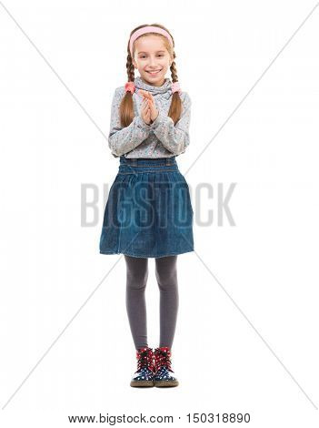 cute little girl standing and rubbing her hands isolated on white background