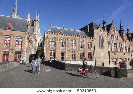 Maarssen, Netherlands, 30 september 2016: people walk and ride bike on old bridge near Burg in the medieval town of bruges in belgium with blue sky on summer morning