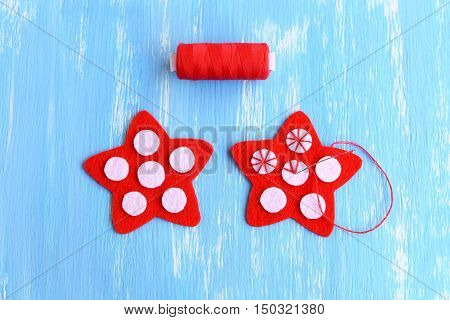 Sewing red Christmas star diy. How to sew on a white felt balls to a red felt stars. Decorative stitch. Christmas diy idea for kids and beginners. Step. Manual. Top view. Closeup