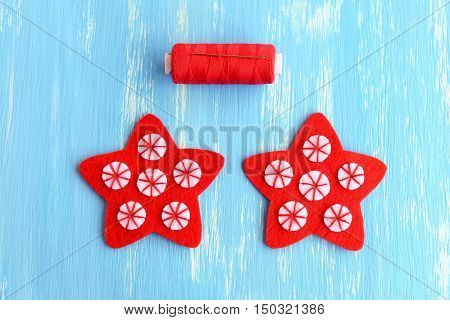 Sewing red Christmas star diy. Sew the white felt circles to the red felt stars using red thread. Simple kids Christmas diy. Winter hobby. Sewing instructions. Step. Top view. Closeup