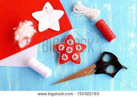 Felt Christmas star diy, paper pattern pinned to red felt sheet, scissors, thread, needle, cord on blue wooden background. Christmas background. Winter sewing diy for children and beginners
