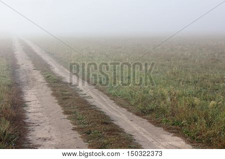 old empty road through the field disappearing into the thick fog / journey into the unknown