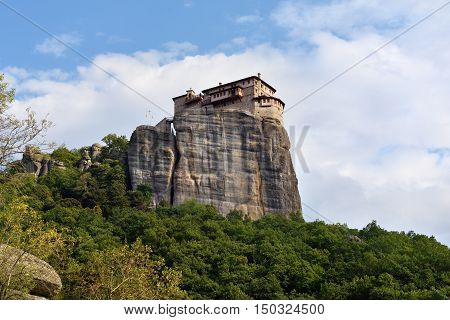 View from bottom on the Holy Monastery Roussanov at sunset time Meteora Greece