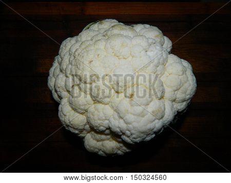Large white cauliflower head on a dark background.