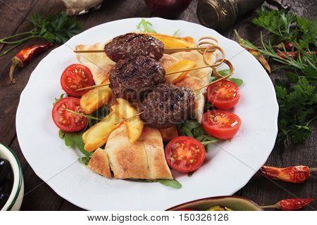 Turkish kofta kebab, minced meat skewer with fried potatoes and flatbread