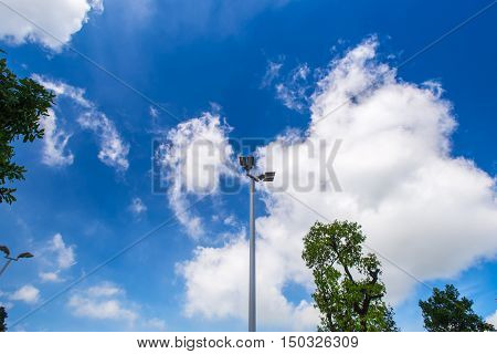 Illuminated street light lamp post against blue sky background